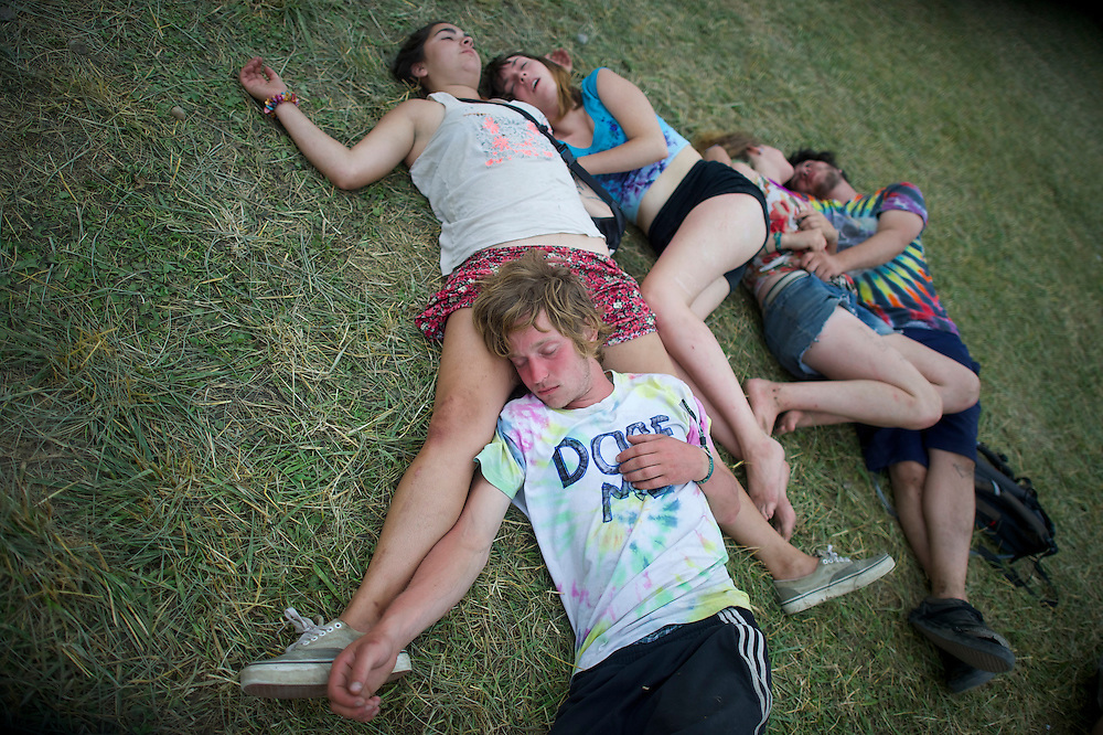 Revelers sleep in a group on the concert grounds during the Firefly Music Festival in Dover, DE on June 21, 2014.  The four day festival is set at a 105 acre grounds at the Dover International Speedway and many well known bands perform.