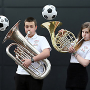 L to R : Ross Pearce (Tuba) and Kirsty Mason ( French Horn). The 30-strong Senior Wind Band from Hermitage Academy in Helensburgh play it for laughs as they prepare to go on tour to Spain during the World Cup in their smart new tops from their sponsors Iomart. Lionel Messi is master of keepie up, but could he keep the ball up with a French Horn? Picture Robert Perry 22nd May 2014<br /> <br /> Must credit photo to Robert Perry<br /> <br /> Image is free to use in connection with the promotion of the above company or organisation. 'Permissions for ALL other uses need to be sought and payment make be required.<br /> <br /> <br /> Note to Editors:  This image is free to be used editorially in the promotion of the above company or organisation.  Without prejudice ALL other licences without prior consent will be deemed a breach of copyright under the 1988. Copyright Design and Patents Act  and will be subject to payment or legal action, where appropriate.<br /> www.robertperry.co.uk<br /> NB -This image is not to be distributed without the prior consent of the copyright holder.<br /> in using this image you agree to abide by terms and conditions as stated in this caption.<br /> All monies payable to Robert Perry<br /> <br /> (PLEASE DO NOT REMOVE THIS CAPTION)<br /> This image is intended for Editorial use (e.g. news). Any commercial or promotional use requires additional clearance. <br /> Copyright 2014 All rights protected.<br /> first use only<br /> contact details<br /> Robert Perry     <br /> 07702 631 477<br /> robertperryphotos@gmail.com<br />        <br /> Robert Perry reserves the right to pursue unauthorised use of this image . If you violate my intellectual property you may be liable for  damages, loss of income, and profits you derive from the use of this image.