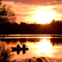 Two men motor across the still surface of Wingfoot Lake looking for a spot to fish as dusk approaches. Hartville, Ohio.