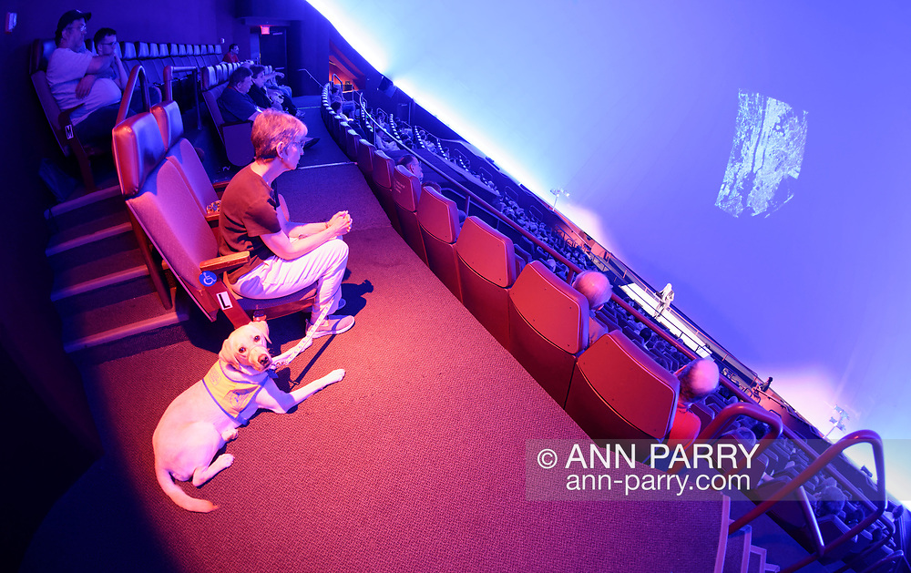 Garden City, New York, USA. June 21, 2018. Space Shuttle Astronaut MIKE MASSIMINO, a Long Island native, gives free lecture in JetBlue Sky Theater Planetarium at the Cradle of Aviation Museum. Seated in audience at left is volunteer puppy raiser FLORENCE SCARINCI with dog she is training from Canine Companions for Independence, a Medford organization. Evening with Mike Massimino lecture is part of the museum's Countdown to Apollo at 50, celebrating 50th anniversary of Apollo 11 moon landing on July 20, 1969.