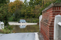 Buttsbury, Essex. 13th October 2014.  Vehicles driving through flooded roads near Buttsbury in Essex after overnight torrential rain.