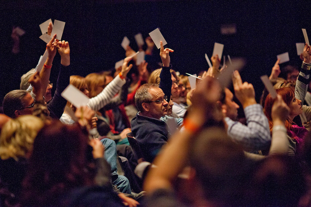 Audience members raise cards in the air as Iowa magician Nate Staniforth performs magic tricks before discussing his approach to performing at The Englert Theater in Iowa City, Iowa on Friday, November 6, 2015 during the Witching Hour Festival.