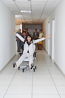 Office workers playing on office chairs in hallway