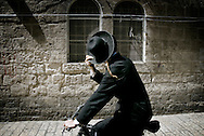 A Jewish Orthodox covers himself as he runs with a bycicle through Jerusalem's Old City, April 15, 2010.