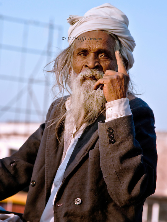 Half length portrait of a Gujarati Jain man in white turban and shabby suit jacket. left hand raised with upright forefinger.  He has a long white beard.