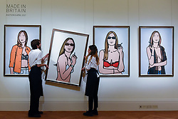 "© Licensed to London News Pictures. 31/03/2017. London, UK. Technicians hang ""Ruth Smoking"", 2006, by Julian Opie (Est. GBP 30-50k).  Press preview of ""Made in Britain"" at Sotheby's in New Bond Street.  The auction on 5 April celebrates innovative British art in the twentieth century as well as artwork by political cartoonist Gerald Scarfe. Photo credit : Stephen Chung/LNP"