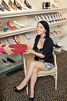 Mid adult woman customer taking footwear box from female salesperson