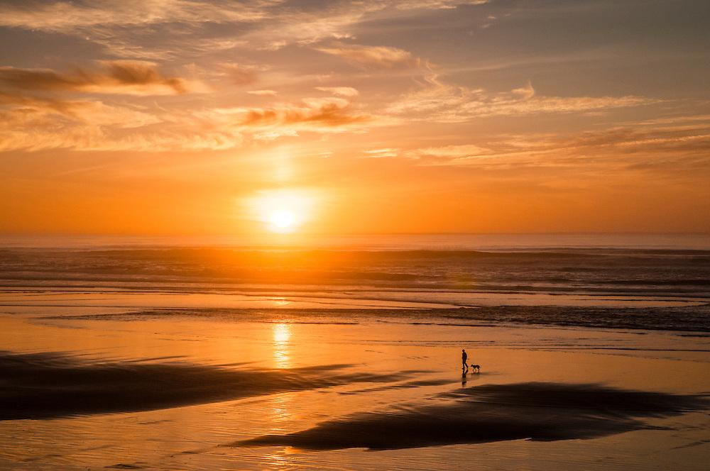 Woman walking dog at sunset on Tillicum Beach, central Oregon coast.