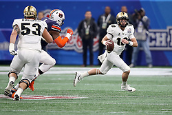 UCF Knights quarterback McKenzie Milton (10) rolls out on a pass play during the 2018 Chick-fil-A Peach Bowl NCAA football game against the Auburn Tigers on Monday, January 1, 2018 in Atlanta. (Jason Parkhurst / Abell Images for the Chick-fil-A Peach Bowl)
