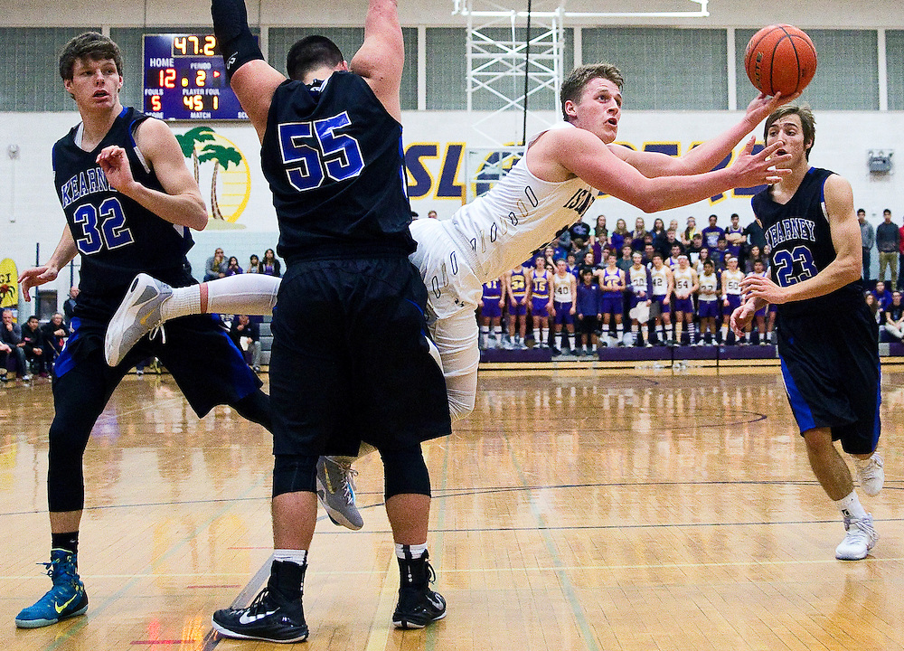 Grand Island Senior High's Pierce Almond shoots as Kearney's Brian Arp (55), Austin Mishou (23) and Kyle Andersen (32) defend during the second quarter of Saturday's game in Grand Island. Senior High defeated Kearney 41-34 after one period of overtime. (Independent/Matt Dixon)