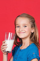 Portrait of young girl holding glass of milk against red background