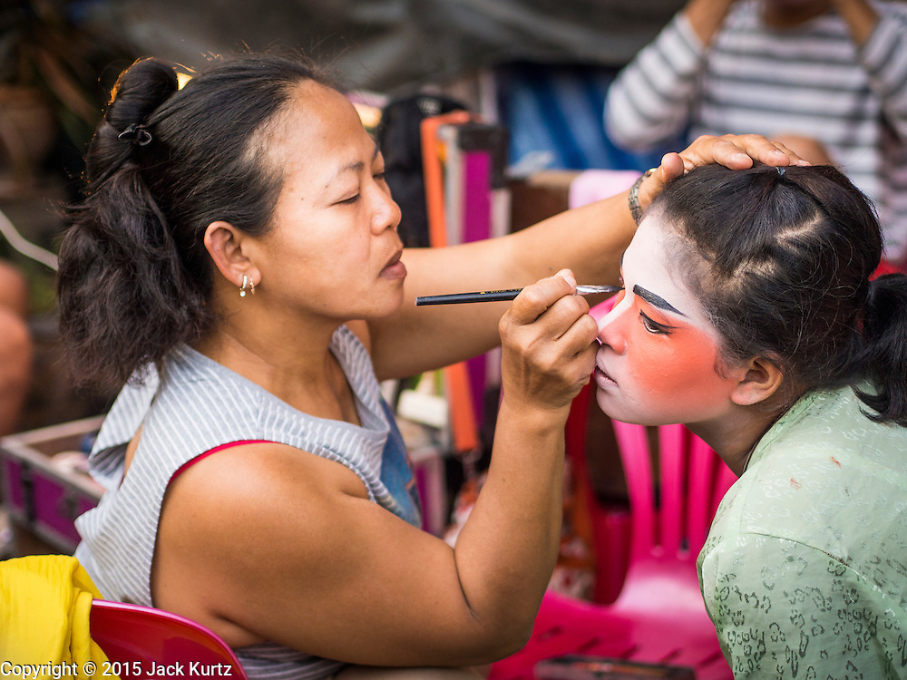 18 JANUARY 2015 - BANGKOK, THAILAND:  Performers with Sai Yong Hong Teochew Opera Troupe help each other get ready for a performance at the Chaomae Thapthim Shrine, a Chinese shrine in a working class neighborhood of Bangkok near the Chulalongkorn University campus. The troupe's nine night performance at the shrine is an annual tradition and is the start of the Lunar New Year celebrations in the neighborhood. The performance is the shrine's way of thanking the Gods for making the year that is ending a successful one. Lunar New Year, also called Chinese New Year, is officially February 19 this year. Teochew opera is a form of Chinese opera that is popular in Thailand and Malaysia.             PHOTO BY JACK KURTZ