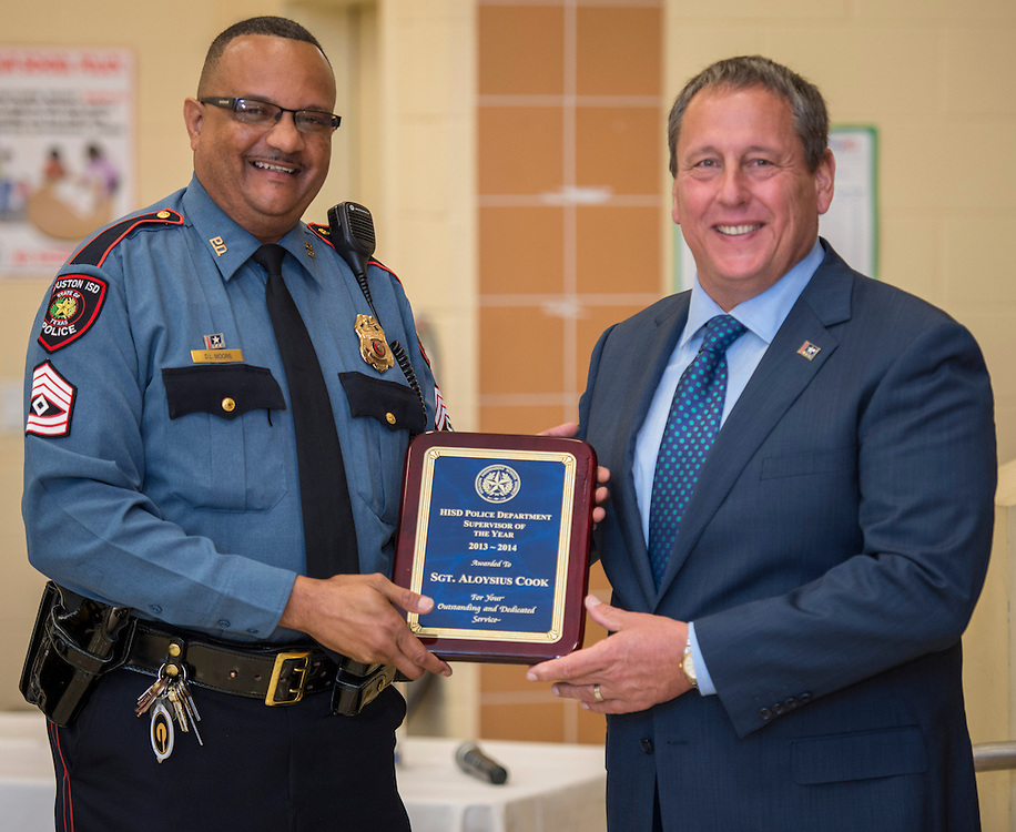 Officer D.L. Moore, left, accepts the Supervisor of the Year award from Chief Robert Mock, right, on behalf of Sgt. Aloysius Cook during the Houston ISD Police awards banquet at Thompson Elementary School, August 15, 2014.