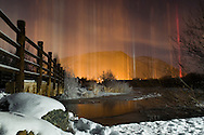 "NEWS&GUIDE PHOTO / PRICE CHAMBERS.A phenomanon known as ""light pillars"" is reflected off Flat Creek on a chilly December night. The colorful columns form when light from the ground reflects off flat snow crystals descending through very cold air."