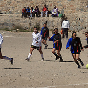 'Attitude at Altitude' Football in Potosi, Bolivia..Girls play football during the Liga Deportiva San Cristobal finals matches on the stone and gravel surface high in the hills over Potosi. Potosi, Bolivia 9th May 2010....'Attitude at Altitude' Football in Potosi, Bolivia'..The Calvario players greet the final whistle with joyous celebration, high fives and bear hugs the players are sprayed with local Potosina beer after a monumental 3-1 victory over arch rivals Galpes S.C. in the Liga Deportiva San Cristobal. The Cup Final, high in the hills over Potosi. Bolivia, is a scene familiar to many small local football leagues around the world, only this time the game isn't played on grass but a rock hard earth pitch amongst gravel and boulders and white lines that are as straight as a witches nose, The hard surface resembles the earth from Cerro Rico the huge mountain that overlooks the town. .. Sitting at 4,090M (13,420 Feet) above sea level the small mining community of Potosi, Bolivia is one of the highest cities in the world by elevation and sits 'sky high' in the hills of the land locked nation. ..Overlooking the city is the infamous mountain, Cerro Rico (rich mountain), a mountain conceived to be made of silver ore. It was the major supplier of silver for the spanish empire and has been mined since 1546, according to records 45,000 tons of pure silver were mined from Cerro Rico between 1556 and 1783, 9000 tons of which went to the Spanish Monarchy. The mountain produced fabulous wealth and became one of the largest and wealthiest cities in Latin America. The Extraordinary riches of Potosi were featured in Maguel de Cervantes famous novel 'Don Quixote'. One theory holds that the mint mark of Potosi, the letters PTSI superimposed on one another is the origin of the dollar sign...Today mainly zinc, lead, tin and small quantities of silver are extracted from the mine by over 100 co operatives and private mining companies who still mine the mountain in poor working condi