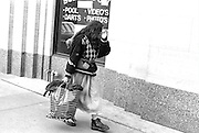 Bag lady age 35 walking by pool hall with shopping bag wearing boots.  St Paul Minnesota USA