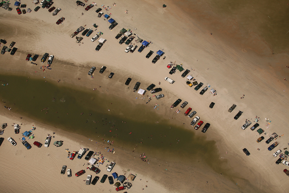 Cars and trucks parked on the North end of Carolina Beach, NC, one of the few public beaches that allows Personally Owned Vehicles to dive on the sand. As of 2009, the public is allowed to purchase a permit to drive on the sand but some environmental groups are attempting to change this policy.