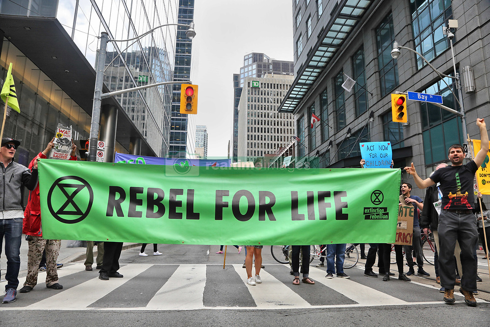 May 24, 2019 - Toronto, ONTARIO, CANADA - Activists from Extinction Rebellion Toronto and other environmental groups block Bay Street in the financial district as they rally outside the Barclays bank office building in Toronto, Ontario, Canada, on May 24, 2019 to protest against climate change and to call for Barclays to stop funding new fossil fuel projects and to start phasing out existing investments in the fossil fuel sector. Barclays is a British multinational investment bank and financial services company with offices in Toronto, Canada. (Credit Image: © Creative Touch Imaging Ltd/NurPhoto via ZUMA Press)