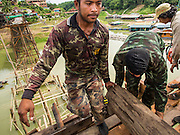 16 SEPTEMBER 2014 - SANGKHLA BURI, KANCHANABURI, THAILAND: A member of the Mon community and a Thai soldier move a piece of lumber on the Mon Bridge. The 2800 foot long (850 meters) Saphan Mon (Mon Bridge) spans the Song Kalia River. It is reportedly second longest wooden bridge in the world. The bridge was severely damaged during heavy rainfall in July 2013 when its 230 foot middle section  (70 meters) collapsed during flooding. Officially known as Uttamanusorn Bridge, the bridge has been used by people in Sangkhla Buri (also known as Sangkhlaburi) for 20 years. The bridge was was conceived by Luang Pho Uttama, the late abbot of of Wat Wang Wiwekaram, and was built by hand by Mon refugees from Myanmar (then Burma). The wooden bridge is one of the leading tourist attractions in Kanchanaburi province. The loss of the bridge has hurt the economy of the Mon community opposite Sangkhla Buri. The repair has taken far longer than expected. Thai Prime Minister General Prayuth Chan-ocha ordered an engineer unit of the Royal Thai Army to help the local Mon population repair the bridge. Local people said they hope the bridge is repaired by the end November, which is when the tourist season starts.    PHOTO BY JACK KURTZ