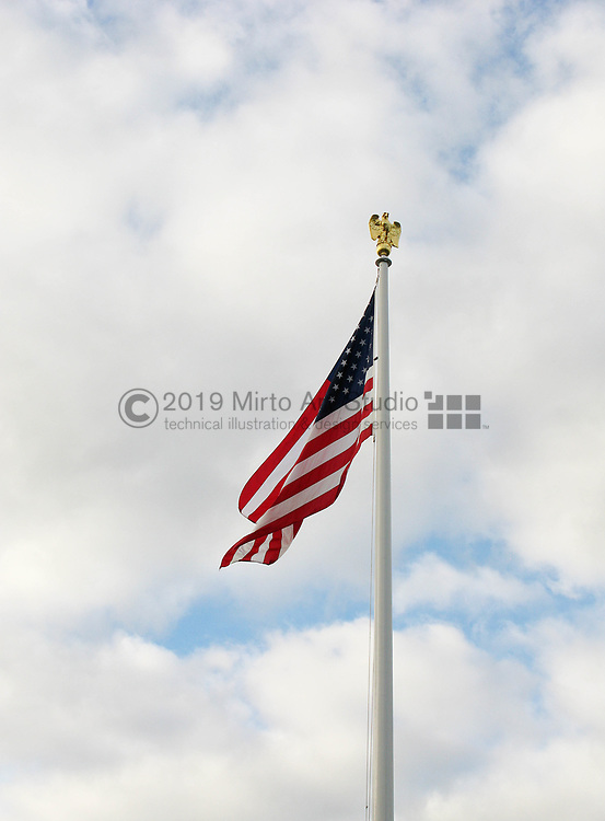 American flag on a flagpole waving in the wind