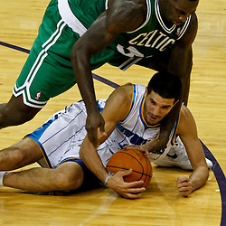 December 28, 2011; New Orleans, LA, USA; New Orleans Hornets guard Greivis Vasquez (21) and Boston Celtics power forward Brandon Bass (30) scramble for a loose ball during the fourth quarter of a game at the New Orleans Arena. The Hornets defeated the Celtics 97-78.  Mandatory Credit: Derick E. Hingle-US PRESSWIRE