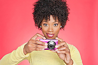 Portrait of an African American woman holding a camera over colored background