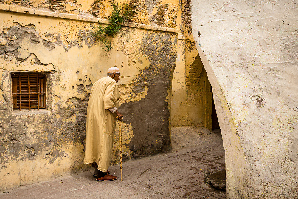 Old man walking in Essaouira medina. Morocco