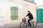 Man riding bicycle past wooden shutters in Les Portes en Re, Ile de Re, France