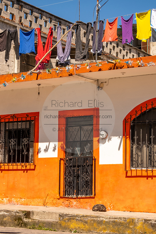 A brightly colored building with colorful washing hanging to dry in Xico, Veracruz, Mexico.