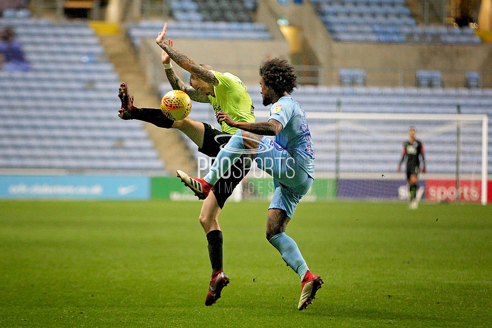 Peterborough United midfielder Marcus Maddison (21) charges down a clearance from Coventry City defender Junior Brown (12) during the EFL Sky Bet League 1 match between Coventry City and Peterborough United at the Ricoh Arena, Coventry, England on 23 November 2018.