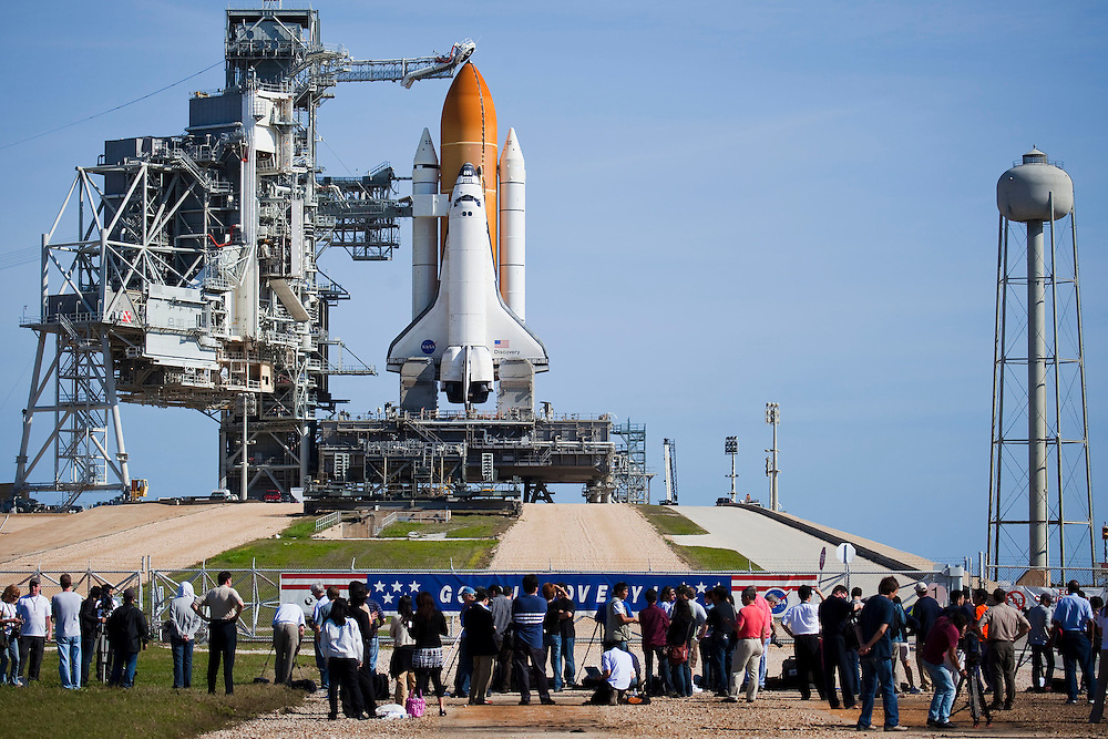 CAPE CANVAERAL, FL -  APRIL 4:  Members of the media photograph Space Shuttle Discovery as it sits on launch pad 39-a as the rotating service structure rolls back at Kennedy Space Center on April 4, 2010, in Cape Canaveral. Discovery is scheduled for a pre-dawn launch on April 5. (Photo by Matt Stroshane/Getty Images)
