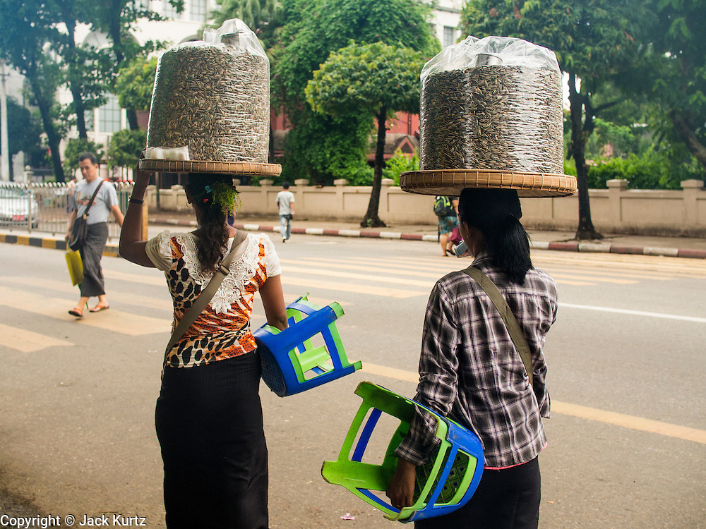 10 JUNE 2014 - YANGON, MYANMAR:   Women who sell watermelon seeds as a snack walk down a street in Yangon, Myanmar.   PHOTO BY JACK KURTZ