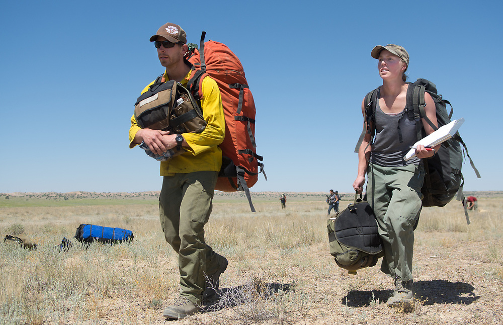 Smokejumpers, Forrest Vogel, left, and Valerie Gill, carry their gear out after jumping out of a Twin Otter from about 3,000 ft., near the Rio Puerco, during a proficiency jump out of Double Eagle II Airport in Albuquerque, N.M., Tuesday, June 29, 2017.  Smokejumpers are the elite wildland firefighters who parachute into remote, inaccessible locations to put fires out, according to a news release from the U.S. Forest Service. About 20 smokejumpers are practicing while waiting to be called to any forest fires in the region. Eight smokejumpers parachuted out of the plane Thursday. To see more photo from the jumps, go to ABQJournal.com. (Marla Brose/Albuquerque Journal)
