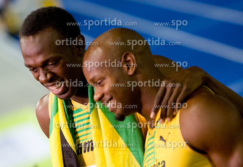 Asafa Powell (R) and Usain Bolt  of Jamaica celebrate winning the gold medal in the mens 4x100 Metres Relay Final with mascot Berlino during day eight of the 12th IAAF World Athletics Championships at the Olympic Stadium on August 22, 2009 in Berlin, Germany. (Photo by Vid Ponikvar / Sportida)
