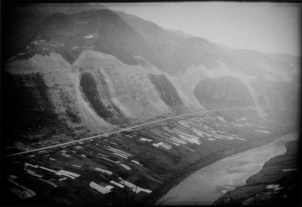 Before: Massive landslips mark the course of new road built along a precipitous flank of the mountains .  Rich fields fill the fertile riverside between Fengjie and Baidicheng, March 2003.