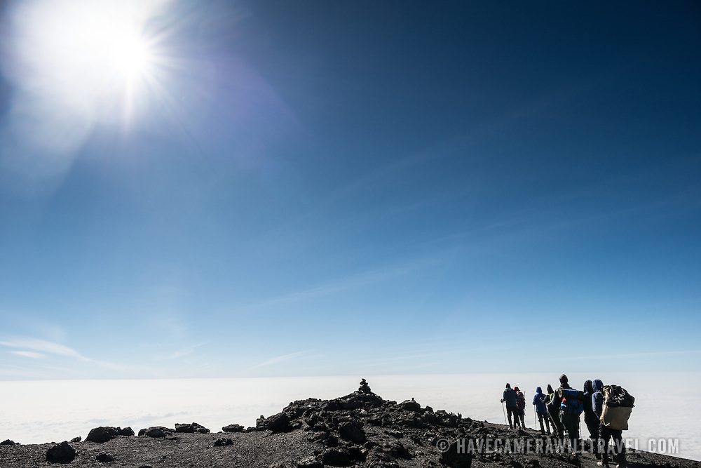 A group of climbers hike on the summit of Mt. Kilimanjaro (Kibo Summit) just after having reached Uhuru Peak, the highest point of Africa.