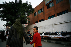 A boy walks with his mother on a street in Giza, just outside Cairo.