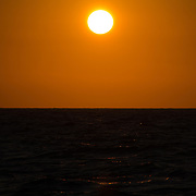 As the sun approaches the horizon over Australia's Great Barrier Reef it creates a rich, golden sky, with rays being reflected off the waves in the water in the foreground. Taken at Swains Reef on the southern end of the Great Barrier Reef of the coast of Queensland, Australia.