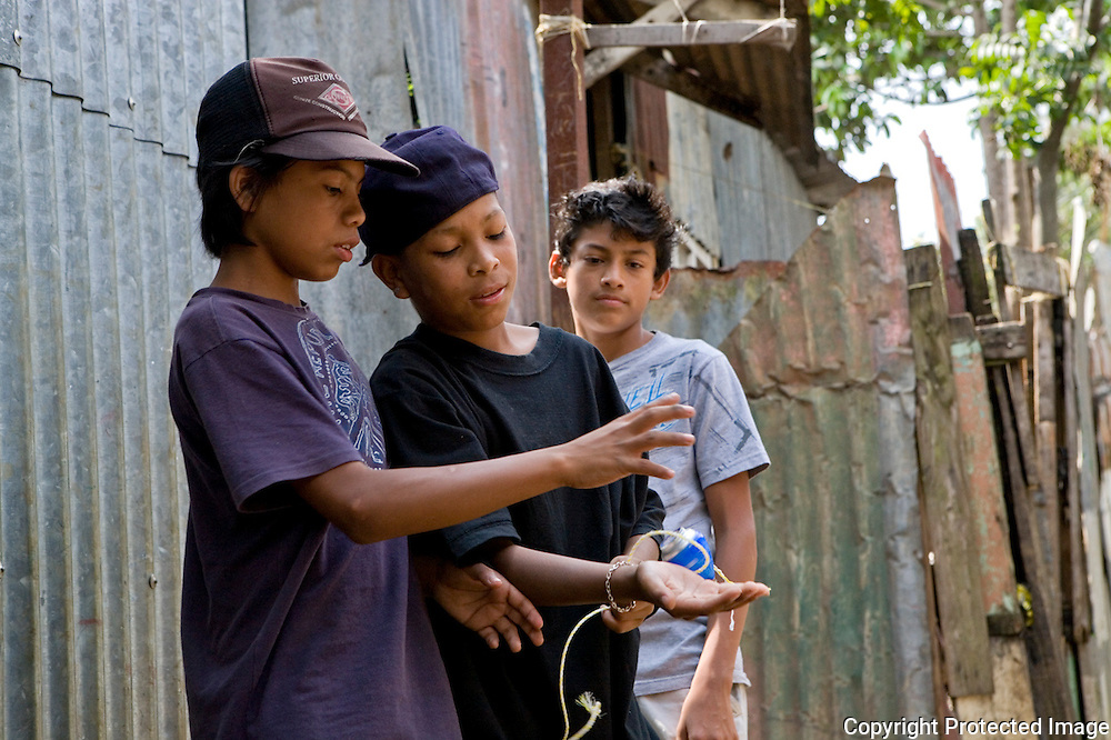 Kevin and two of his friends from San Felipe play with a top in the streets on a Monday morning instead of going to school.