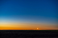 The waning crescent Moon rising in close conjunction with Aldebaran just to the right, and near the Hyades star cluster, all embedded in the twilight over a ripening canola field.<br /> <br /> The Moon occulted Aldebaran from points farther east but by moonrise at my location the two had separated but were still very close. Earthshine lights this dark side of the Moon, despite its low altitude, on this very clear morning. <br /> <br /> Shot the morning of July 10, 2018 from home in southern Alberta. This is a 4-second exposure with the 85mm Rokinon lens at f/2.8 and on the Sony a7III at ISO 400. The ground is a stack of three exposures to smooth noise.