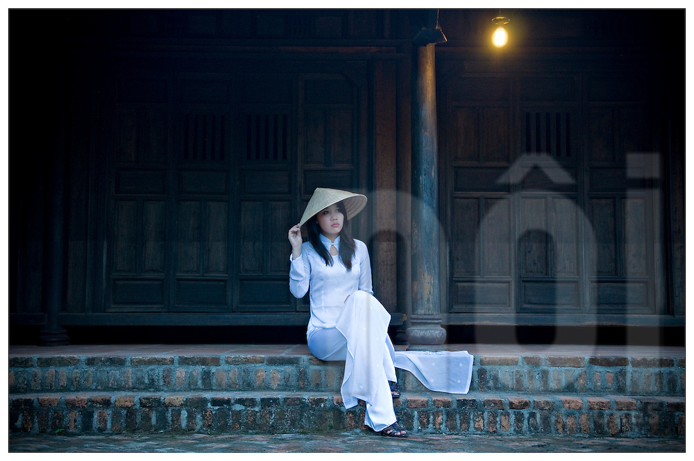 Beauty portrait of a vietnamese woman sitting on steps in front of a pagoda. She wears traditional outfit Ao Dai and conical hat. Khanh Hoa area, Vietnam, Asia