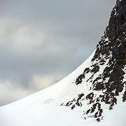 A curved slope of ice and snow leads up to a near-vertical rocky cliff face on one of the dramatic mountains lining the shoreline of the Lemaire Channel in Antarctica.