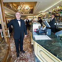 VENICE, ITALY - DECEMBER 02:  The Manager of Caffe Lavena opens the door to welcome customers on December 2, 2011 in Venice, Italy.The Venetian coffee houses have a  long standing history, established at the beginning of 1700 around St. Mark Square have been the centre of cultural meeting and innovations for centuries and served customers like Dickens, Goethe, Casanova and Lord Byron.