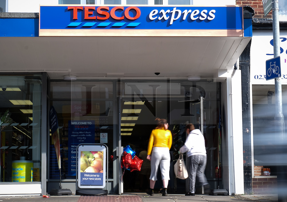 © Licensed to London News Pictures. 05/10/2016. Portsmouth, Hampshire, UK.  People walking into a Tesco Express in Southsea this morning. Tesco PLC, Britain's largest supermarket chain has announced that like-for-like sales had grown in the first half of its financial year. The results come following increased competition in the market from budget supermarkets such as Aldi & Lidl. Photo credit: Rob Arnold/LNP