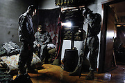 During down time, U.S. Army Spec. Chris Jankowski, Spec. Joshua Philbeck and Staff Sgt. Lawree Washington hang out in the sleeping quarters of an Iraqi police station in Buhriz, Iraq, on Jan. 27, 2007.