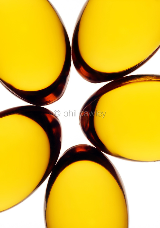 Close up detail of cod liver oil capsules on a white background