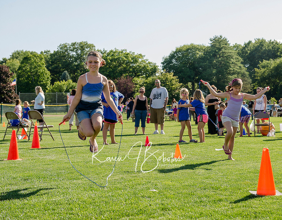 Alexis and Dakota Beaumont race each other in the hoppy game during the Peanut Festival with Opechee Day Camp Thursday evening.  (Karen Bobotas/for the Laconia Daily Sun)