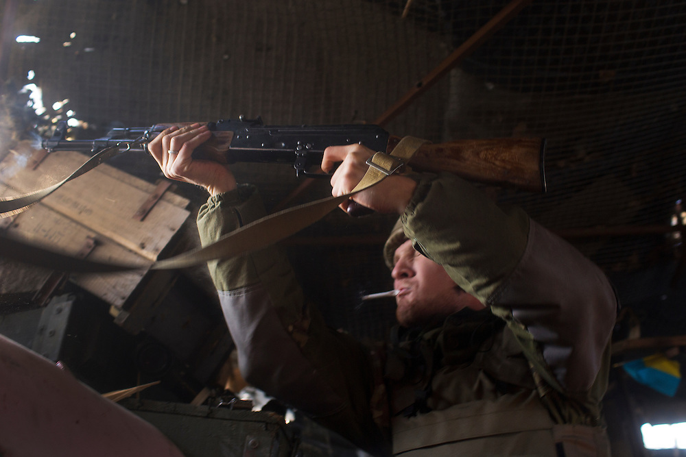 A volunteer fighter with Dnipro-1 battalion dry fires his rifle from his position in a trench on the front on March 20, 2015 in Pisky, Ukraine.