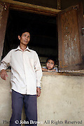 A teacher and student at The Ban Buamlao Primary School in Ban Buamlao, Laos, gaze onto the schoolyard after conclusion of classes. The impoverished school lacks basic learning supplies such as books, paper, and recreational equipment.