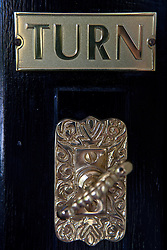 Detailed view of a brass turning door bell on a black door with sign that reads Turn.
